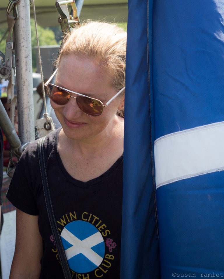 Woman in t-shirt bearing Scottish Club logo, carrying Scottish Flag