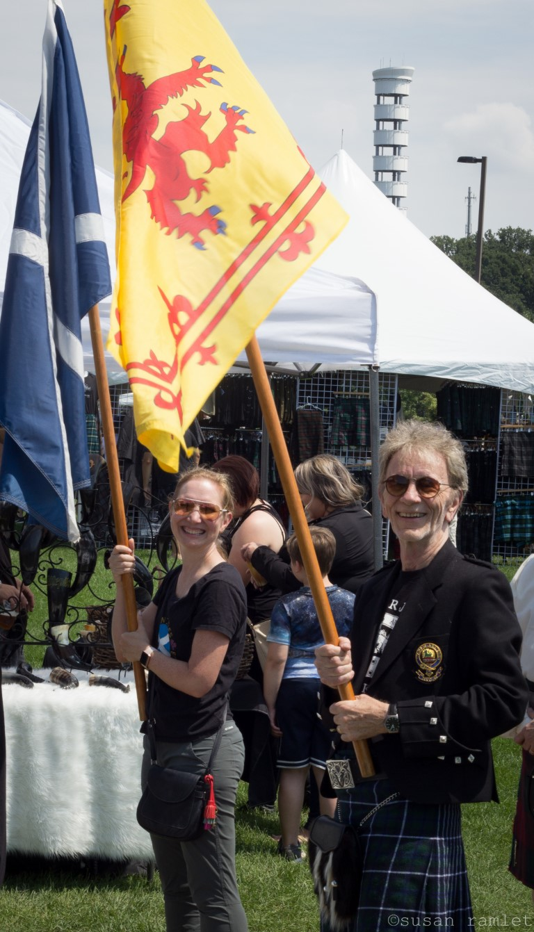 Two people carrying Scottish flags in a parade